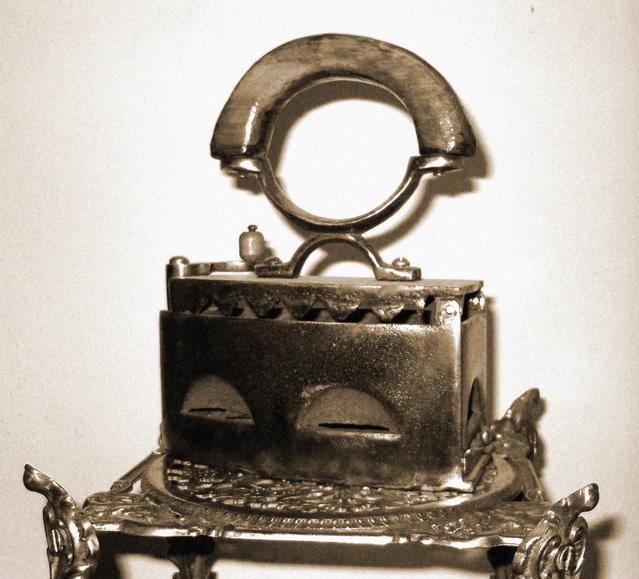dnes již antická žehlička s kovovým držadlem na výstavce